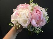 White and pink weddingbouquet made of peonies and lily of the valley