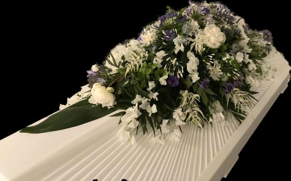 White and blue funeral arrangment for coffin
