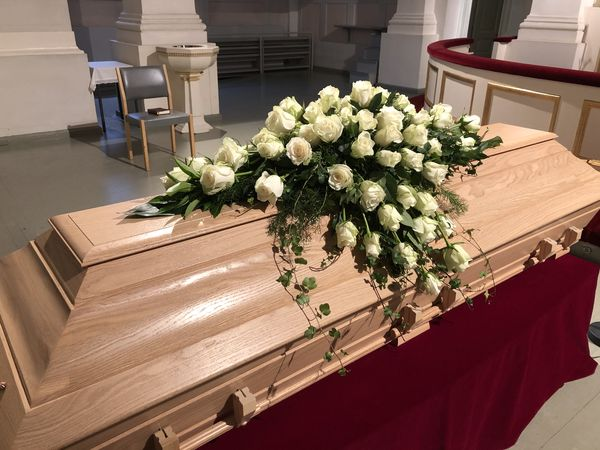 Funeral arrangment for coffin made of white roses