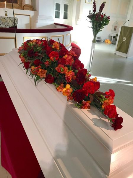 Funeral arrangment for coffin made in red and orange flowers